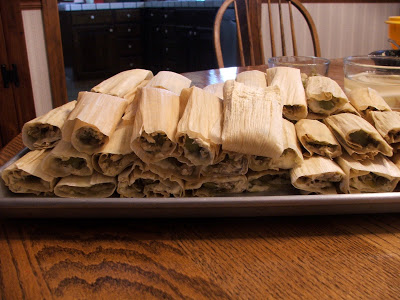 Metal baking sheet sitting on a wood table, with tamales wrapped in corn husks stacked three high
