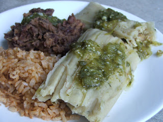 Tamale sitting on a white plate drizzled with green salsa, with a scoop of red rice, and a scoop of refried beans