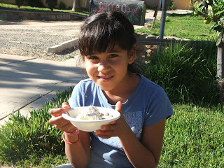 Little girl with black hair and blue shirt holding a bowl of ice cream