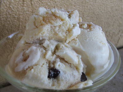 Small glass dish with three small scoops of vanilla ice cream with chocolate chips and cookie dough pieces.