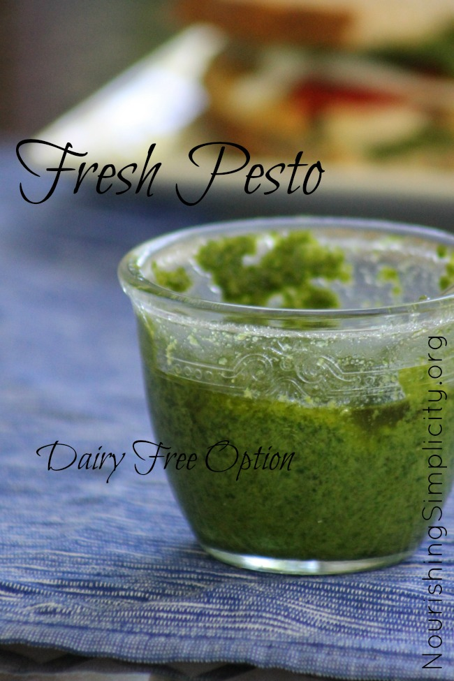 Clear glass dish filled with bright green pesto on a blue placemat.