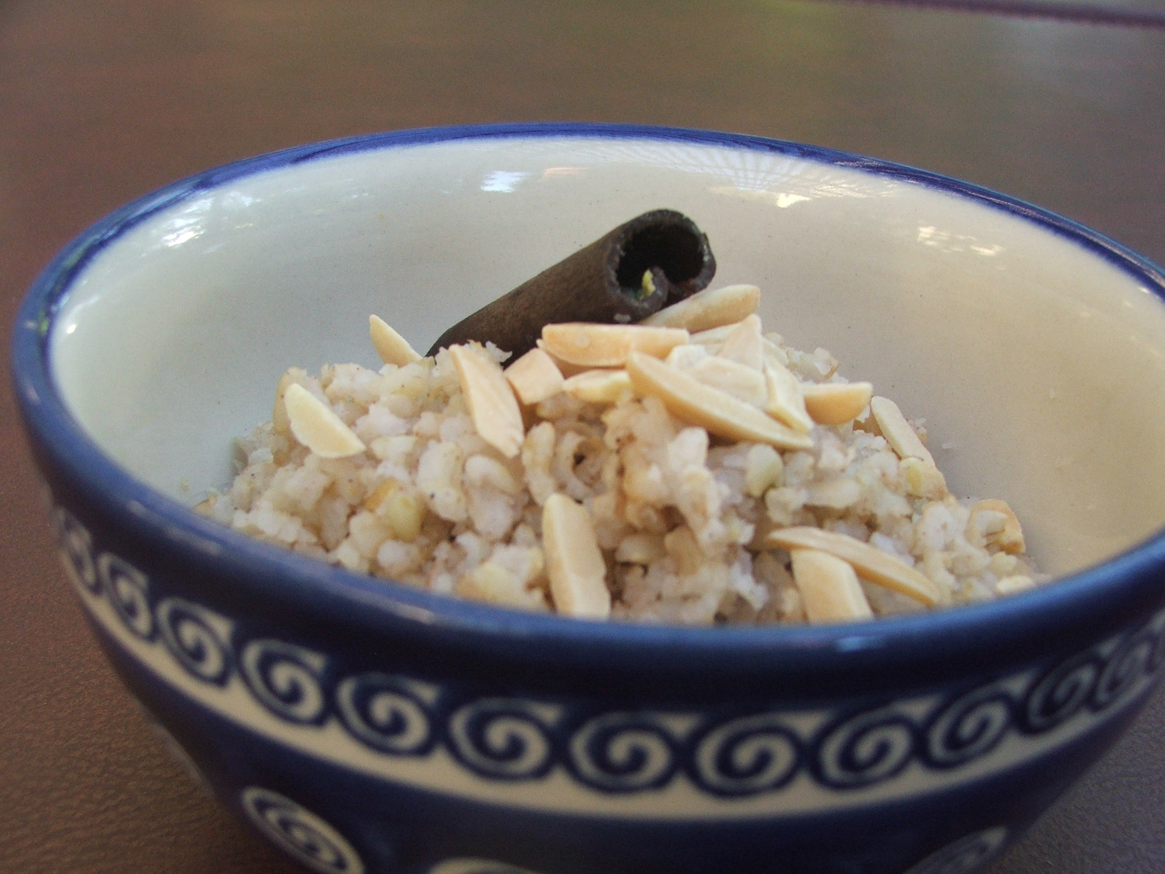 Blue bowl full of rice topped with slivered almonds and a cinnamon stick