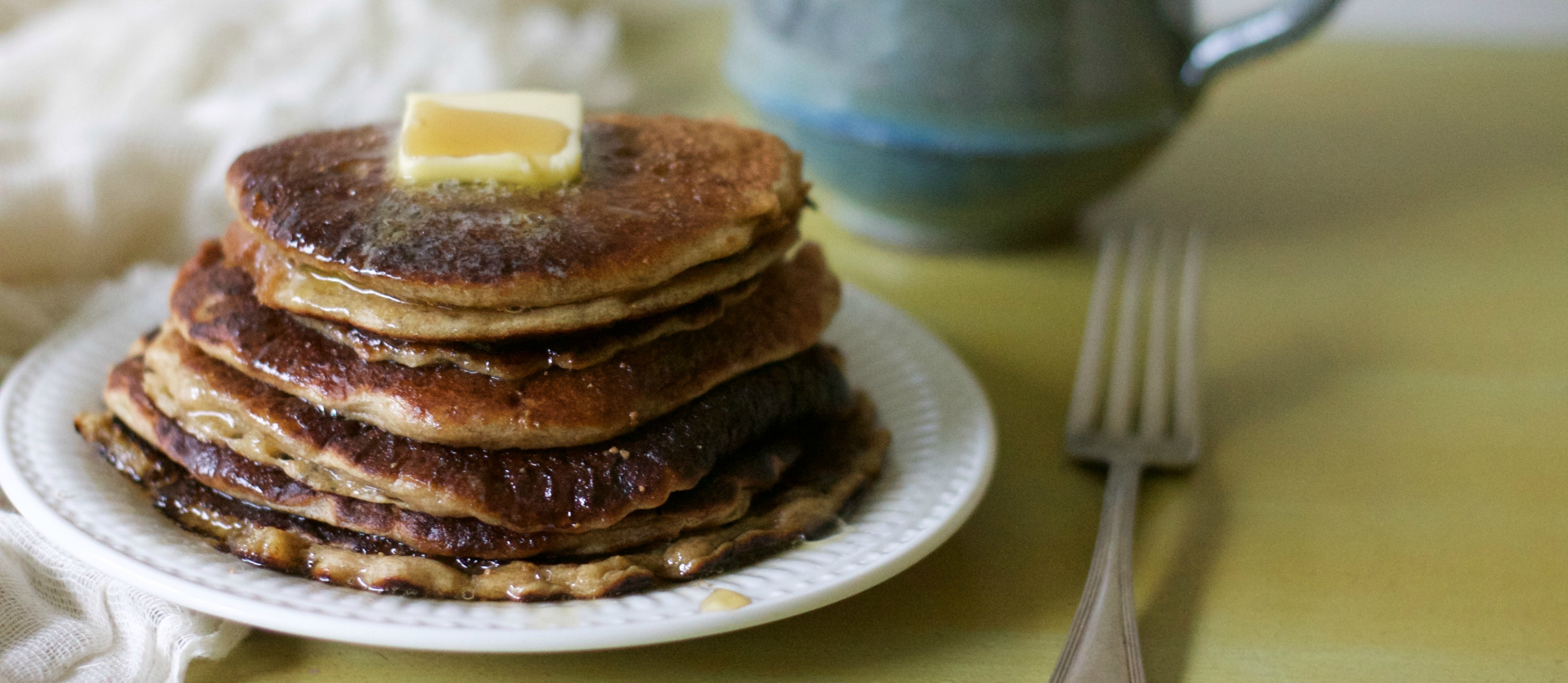 Stack of pancakes topped with butter and syrup on a green table.