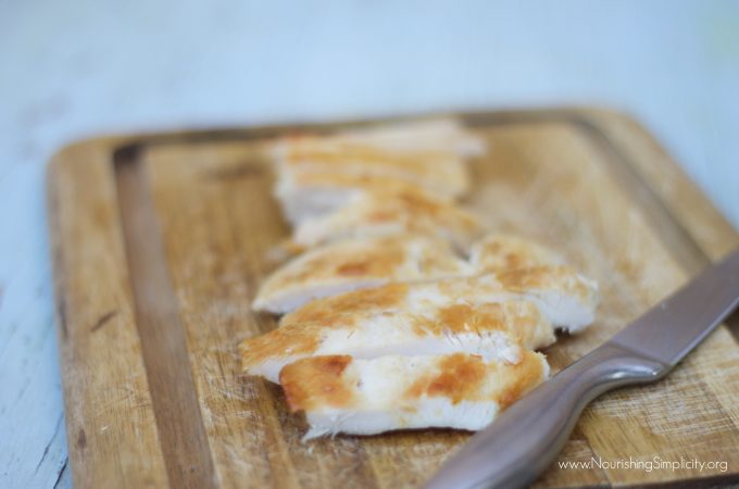 Pan-seared chicken breast on a wooden cutting board with a silver knife.